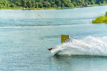 wakeboarder jumps from a springboard behind a rope and makes a wave on the water. Фото со стока
