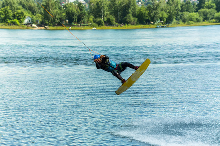 wakeboarder jumps from a springboard behind a rope and makes a wave on the water. Фото со стока - 100411011