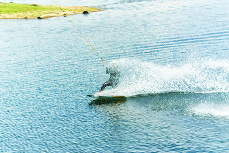 wakeboarder jumps from a springboard behind a rope and makes a wave on the water. Фото со стока - 100411013