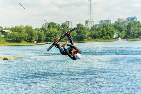 wakeboarder jumps from a springboard behind a rope and makes a wave on the water. Фото со стока - 100411015