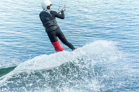 wakeboarder jumps from a springboard behind a rope and makes a wave on the water. Stock Photo