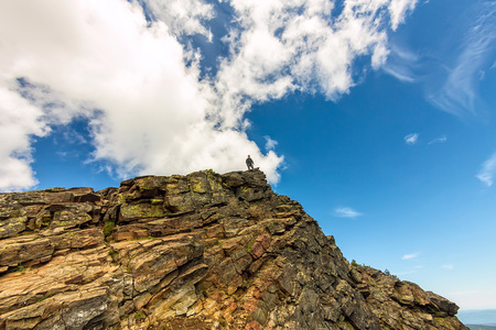 man stands on a steep cliff on the background of the sky.