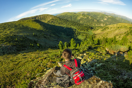 young man with a backpack sits on a rock in the mountains view.