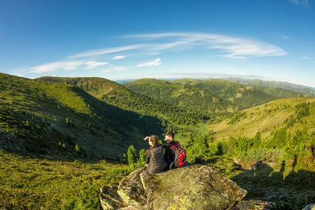 young couple sitting on the rock in the mountains view.