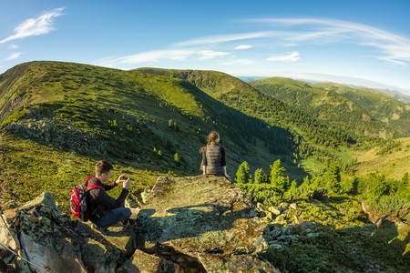 young couple photographed on a rock in the mountains view. Фото со стока