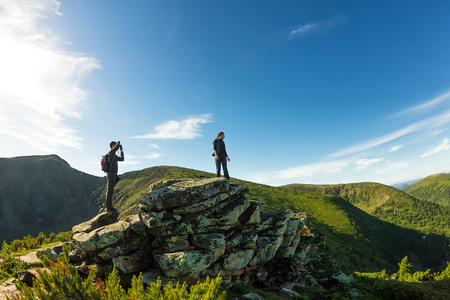 Young couple photographed on a rock in the mountains view.