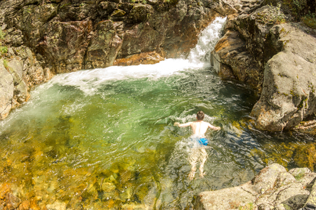 Man swims in the turquoise lagoon of a waterfall in a rocky gorge.