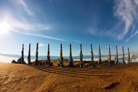 Shaman poles of serge on Olkhon in the sunset with long shadows.