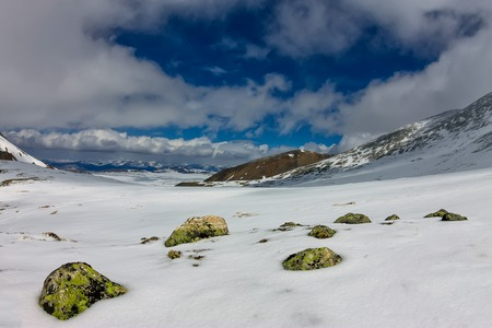 Snowy mountains aero photo drone, clouds approaching peaks and valley. Фото со стока - 101225771