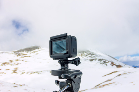 Action camera stands on a tripod against the backdrop of the mountains. Фото со стока