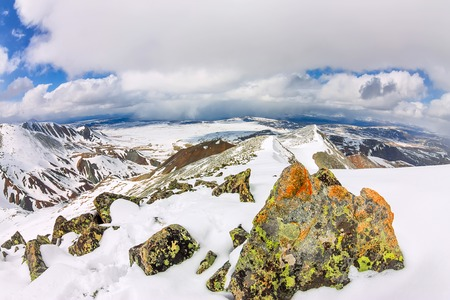 Snowy mountains aero photo drone, clouds approaching peaks and valley.