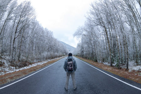 The man in gray with a backpack standing in the center of the gray road in a snowy forest. Фото со стока - 101859456