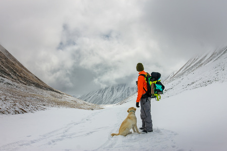 Man and dog labrador hike the cloudy mountains. Фото со стока - 101811183