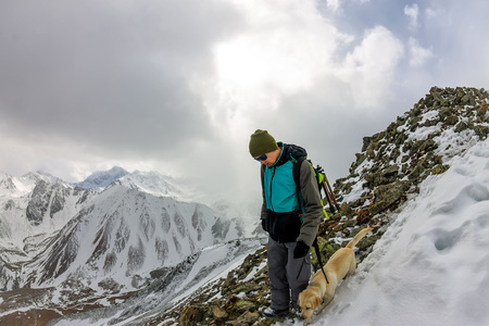 Man and dog labrador hike the cloudy mountains Фото со стока - 105520698