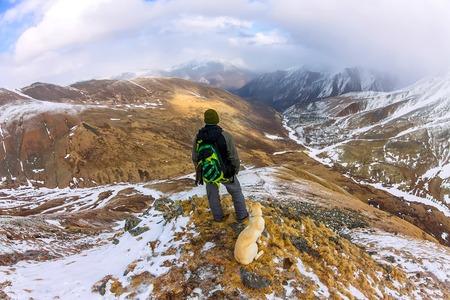 Man and dog labrador hike the cloudy mountains. Фото со стока - 101859472