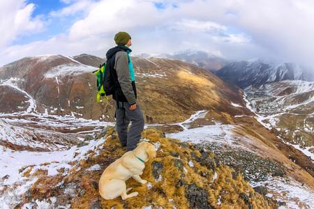 Man and dog labrador hike the cloudy mountains. Фото со стока - 101886964