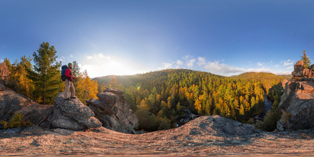 Backpacker on top of a rock fall at dawn. Spherical panorama 360 180 degrees equidistant Фото со стока