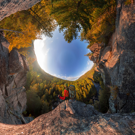 Backpacker on top of a rock fall at dawn. spherical degree panorama 360 180 little planet