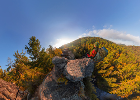 Backpacker on top of a rock fall at dawn. Wide angle aerial panorama.