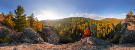 Backpacker on top of a rock fall at dawn. Cylindrical panorama 360 degrees.