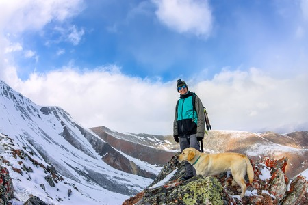Man and dog labrador hike the cloudy mountains.