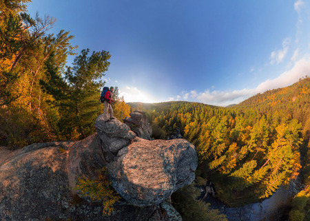 Backpacker on top of a rock fall at dawn. Wide angle aerial panorama. Фото со стока - 103297670