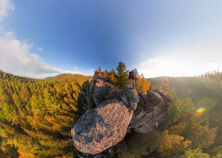 Backpacker on top of a rock fall at dawn. Wide angle aerial panorama Фото со стока