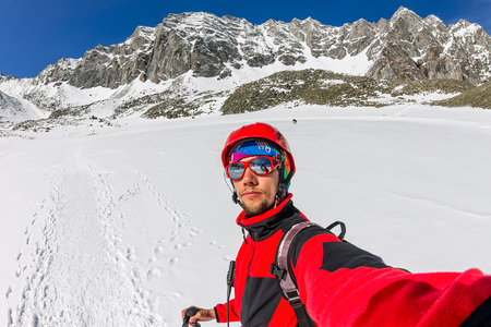 Selfi male mountaineer in snowy mountains, wearing a helmet with a backpack Фото со стока