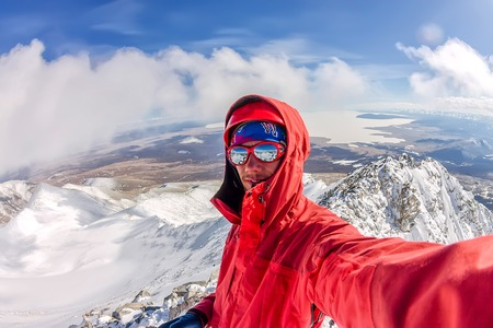 Selfi male mountaineer in snowy mountains, wearing a helmet with a backpack Фото со стока - 105261141