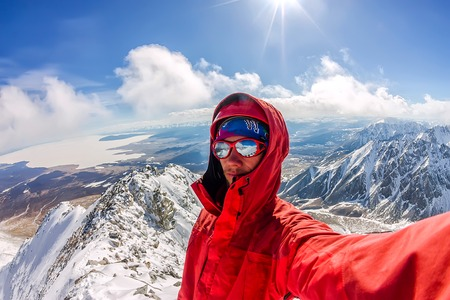 Selfi male mountaineer in snowy mountains, wearing a helmet with a backpack Фото со стока - 105261142