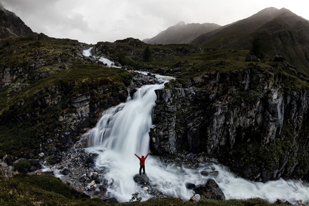 man stands under a mountain waterfall in the misty valley of Iceland Фото со стока