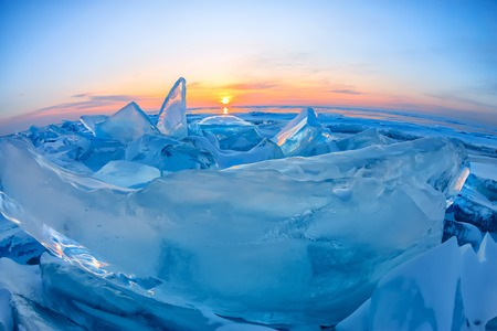 Transparent blue Toros Baikal ice is shining through the crack sunset
