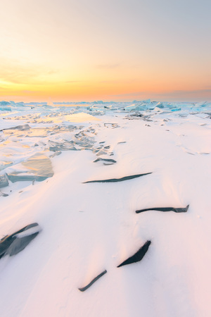 turquoise hummocks under the snow of Lake Baikal at the pink dawn
