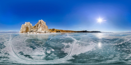 Shaman Rock on Olkhon Island in winter, surrounded by the blue ice of Lake Baikal with cracks. Panorama 360 180 degree