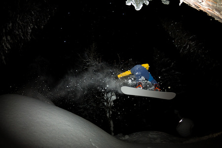 freerider rides at night on powder snow blows up Фото со стока