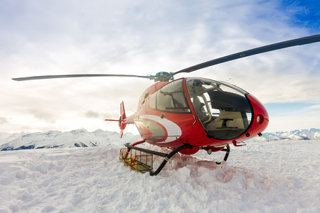 Red rescue helicopter lands standing in snowy mountains Фото со стока - 108955770