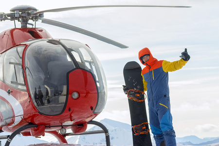 Snowboarder freerider is standing at the helicopter in the snowy mountains in winter under the clouds Фото со стока - 108775222