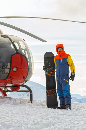 Snowboarder freerider is standing at the helicopter in the snowy mountains in winter under the clouds Фото со стока