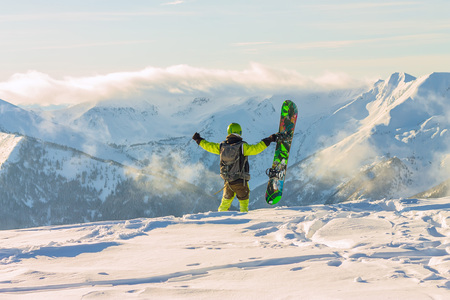 Snowboarder freerider is standing in the snowy mountains in winter under the clouds Фото со стока