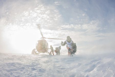 landing from the helicopter skiers freeriders in the snowy mountains in winter Фото со стока