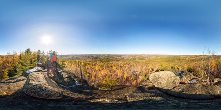 Couple of tourists with backpacks man and woman standing on a rock in autumn forest. Spherical 360vr panorama Imagens
