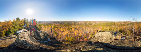 Couple of tourists with backpacks man and woman standing on a rock in autumn forest. Cylindrical 360 panorama Imagens