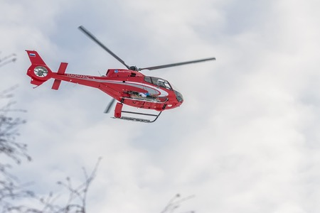 Red rescue helicopter fly in snowy mountains