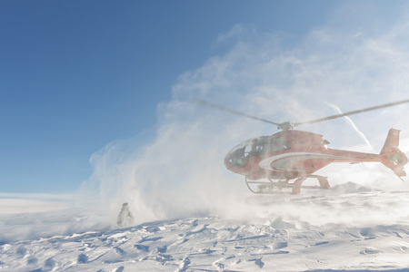 Heliski helicopter takes off in snow powder freeride landed on mountain Фото со стока