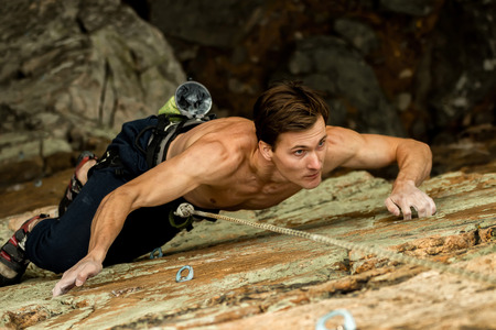 Rock climber climbs on a cliff on a rope, top view