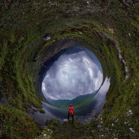 man stands by lake in red jacket in cloudy weather. tiny planet 360