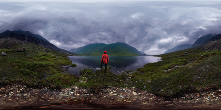 man stands by lake in red jacket in cloudy weather. Spherical panorama 360vr