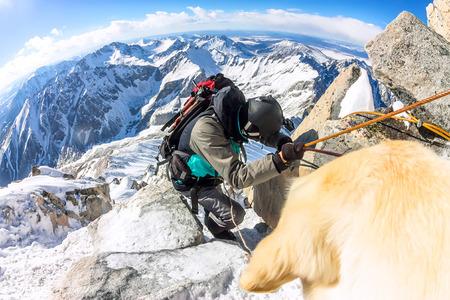 Man and dog labrador hike the cloudy mountains Фото со стока