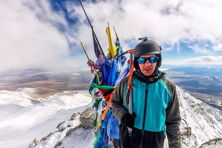 portrait man mountaineer in snowy mountains, wearing a helmet