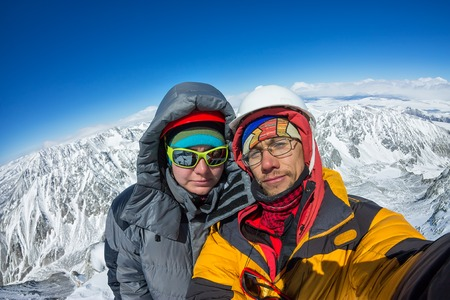 Selfie couple climber in helmet and down jacket stand on top of mountain